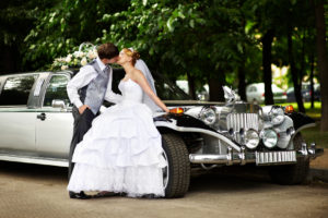 Happy groom adn bride about retro limousine